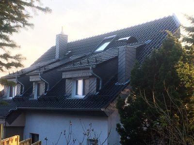 Dachsanierung mit Braas Rubin 11V. Gauben und Kamine mit Schiefer verkleidet.