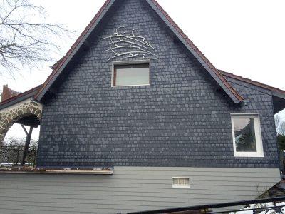 Fassadenbekleidung mit 20x20 Bogenschnitt Schiefern und einer Sockelverkleidung mit Eternit Cedral Dielen